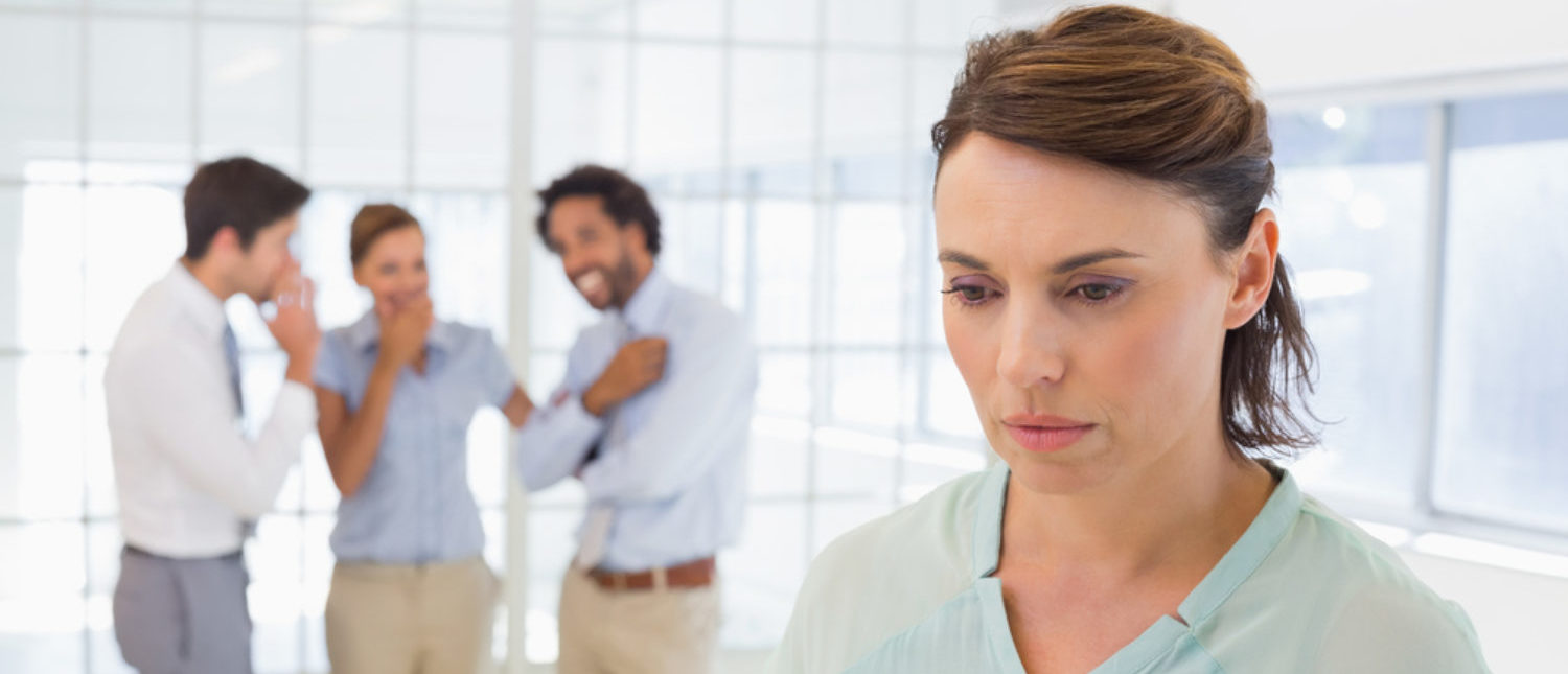 Colleagues gossiping with sad young businesswoman.  [Shutterstock - lightwavemedia]
