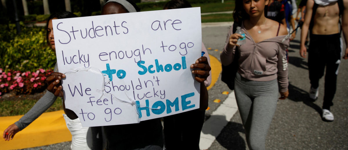 Students from West Boca Raton Community High School carry a placard as they walk to Marjory Stoneman Douglas High School, during a protest to show support, following a mass shooting in Parkland, Florida, U.S., February 20, 2018. REUTERS/Carlos Garcia Rawlins