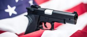 A gun wrapped in an American flag. (Shutterstock)