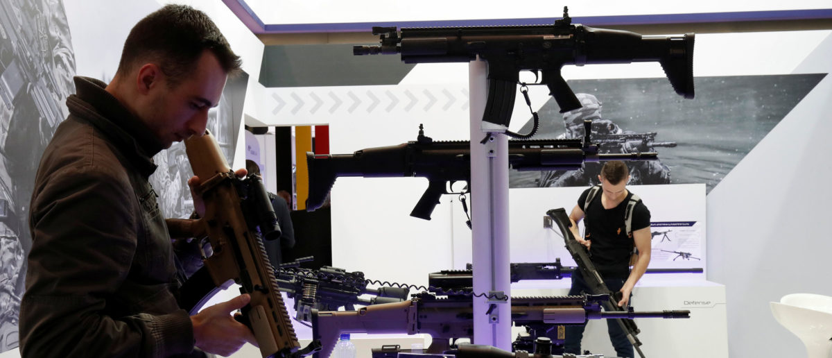Gun enthusiasts look over FN Herstal rifles that are displayed at the 20th Paris Milipol, the worldwide exhibition dedicated to homeland security, in Villepinte, near Paris, France, November 21, 2017. REUTERS/Benoit Tessier