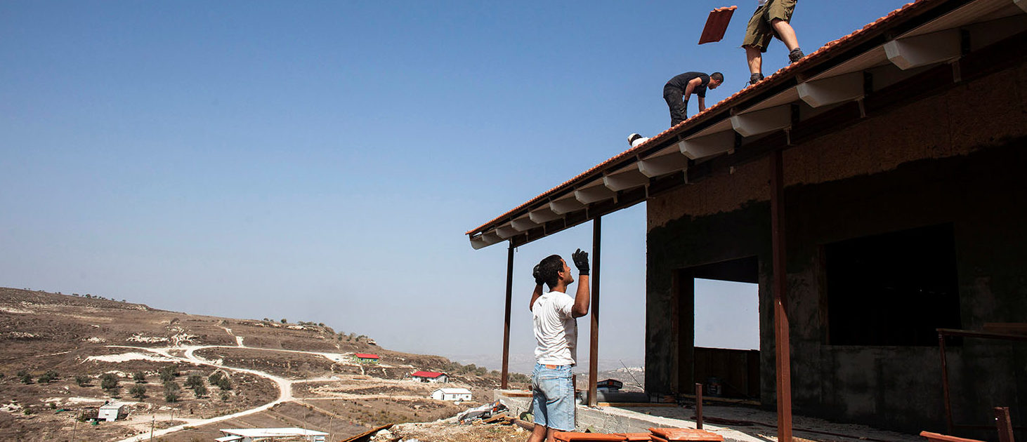 Men work on the roof of a house under construction in the unauthorised Jewish settler outpost of Havat Gilad, south of the West Bank city of Nablus November 5, 2013. REUTERS/Nir Elias/File Photo