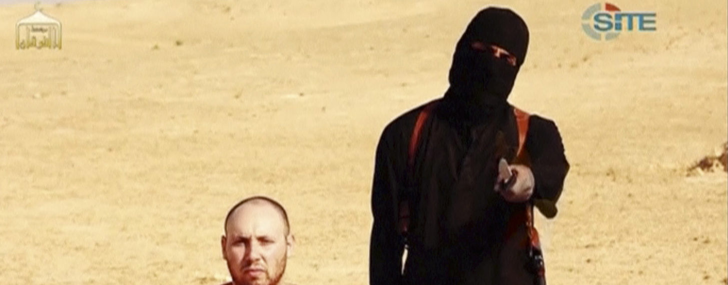 "A masked, black-clad militant, who has been identified by the Washington Post newspaper as a Briton named Mohammed Emwazi, stands next to a man purported to be Steven Sotloff in this still image from a video obtained from SITE Intel Group website February 26, 2015. The ""Jihadi John"" killer who has featured in several Islamic State beheading videos is Emwazi, a Briton from a middle class family who grew up in London and graduated from college with a degree in computer programming, the Washington Post newspaper said. In videos released by Islamic State (IS), the masked, black-clad militant brandishing a knife and speaking with an English accent appears to have carried out the beheadings of hostages including Americans and Britons. The Washington Post said Emwazi, who used the videos to threaten the West and taunt leaders such as President Barack Obama and British Prime Minister David Cameron, was believed to have travelled to Syria around 2012 and to have later joined IS. British government sources and the police refused to confirm or deny the report, citing a live anti-terrorism investigation, a position mirrored by a spokeswoman for Cameron.  REUTERS/SITE Intel Group via Reuters TV"