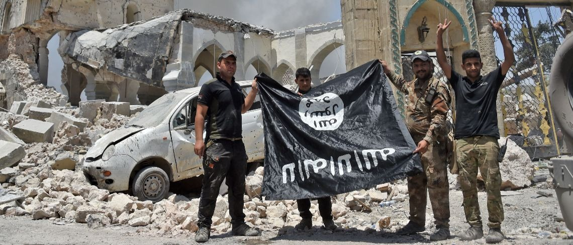 ISIS fighters hold the Islamic State flag (AFP/Getty Images/Fadel Senna)