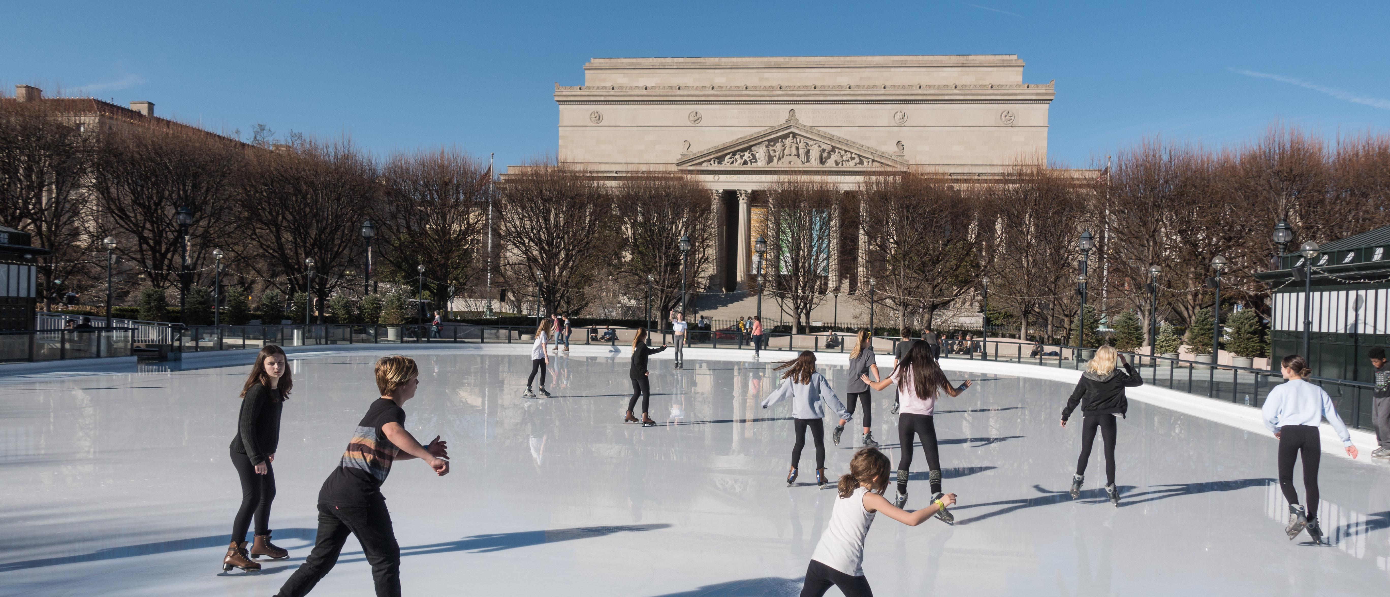 WASHINGTON DC - FEB 23, 2017: Ice skaters dressed for spring skate under 74 degree (F) sun in unseasonably warm winter weather at National Gallery of Art Sculpture Garden Ice Rink on the National Mall. Source: bakdc/Shutterstock