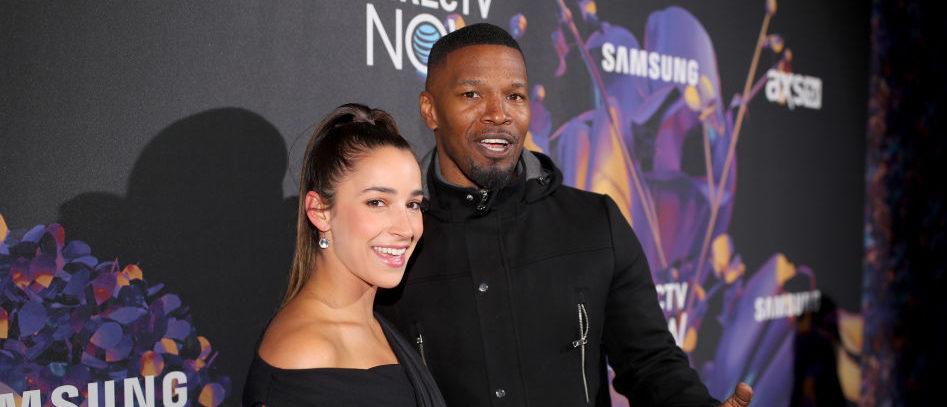 Olympic gymnast Aly Raisman (L) and actor Jamie Foxx attend the 2018 DIRECTV NOW Super Saturday Night Concert at NOMADIC LIVE! at The Armory on February 3, 2018 in Minneapolis, Minnesota. (Photo by Christopher Polk/Getty Images for DirecTV)