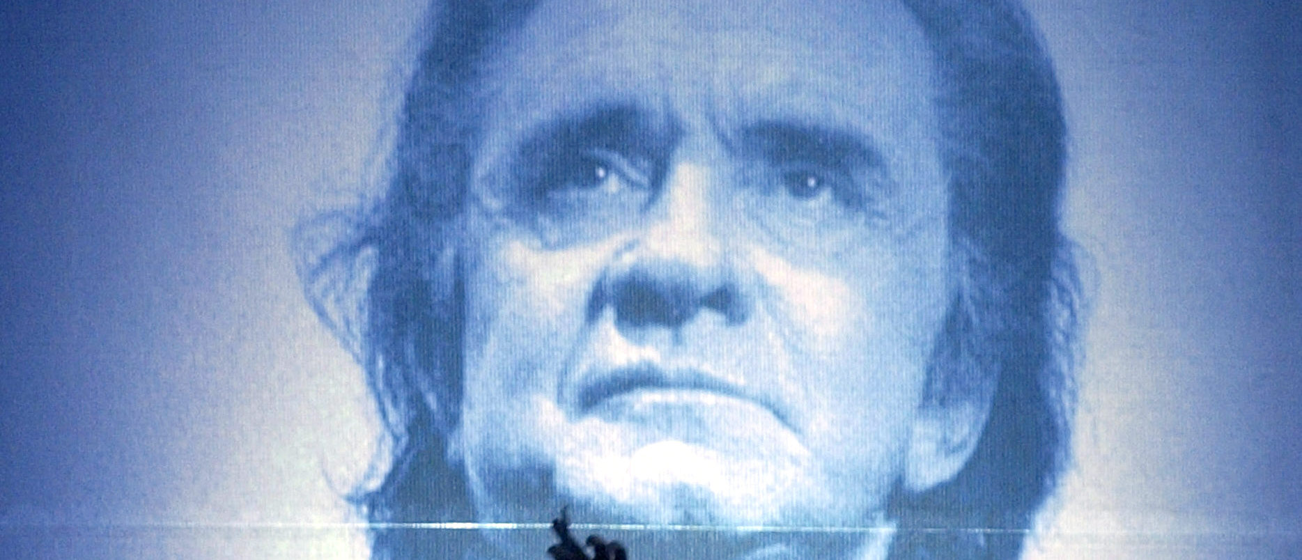 A stage hand at the Ryman Auditorium puts the final touchs on a large photo of the late country music legend Johnny Cash, before the Cash tribute concert in Nashville, Tennessee, late November 10, 2003. Cash died September 12, 2003, at the age of 71 from complications from diabetes. - PBEAHUOMDFS