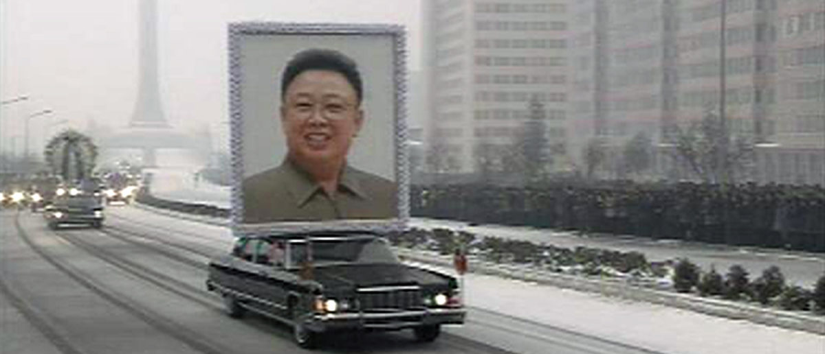 """A limousine carrying a portrait of late North Korean leader Kim Jong-il leads his funeral procession past crowds on a street in Pyongyang in this still image taken from video December 28, 2011. North Korea's military staged a huge funeral procession on Wednesday in the snowy streets of the capital Pyongyang for its deceased """"dear leader,"""" Kim Jong-il, readying a transition to his son, Kim Jong-un. REUTERS/KRT via Reuters TV"""