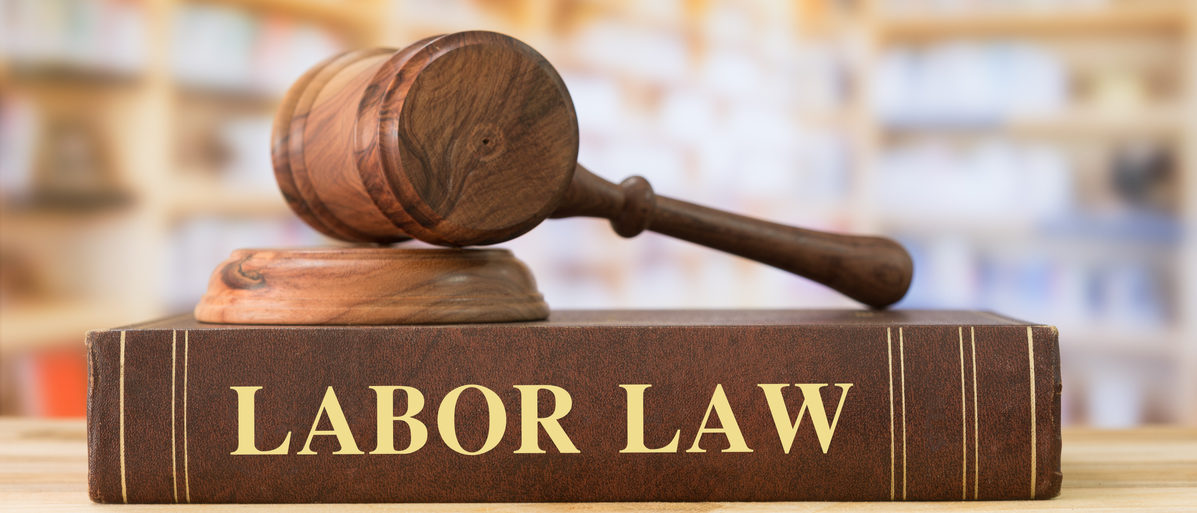 Labor Law books with a judges gavel on desk in the library. Shutterstock/create jobs 51