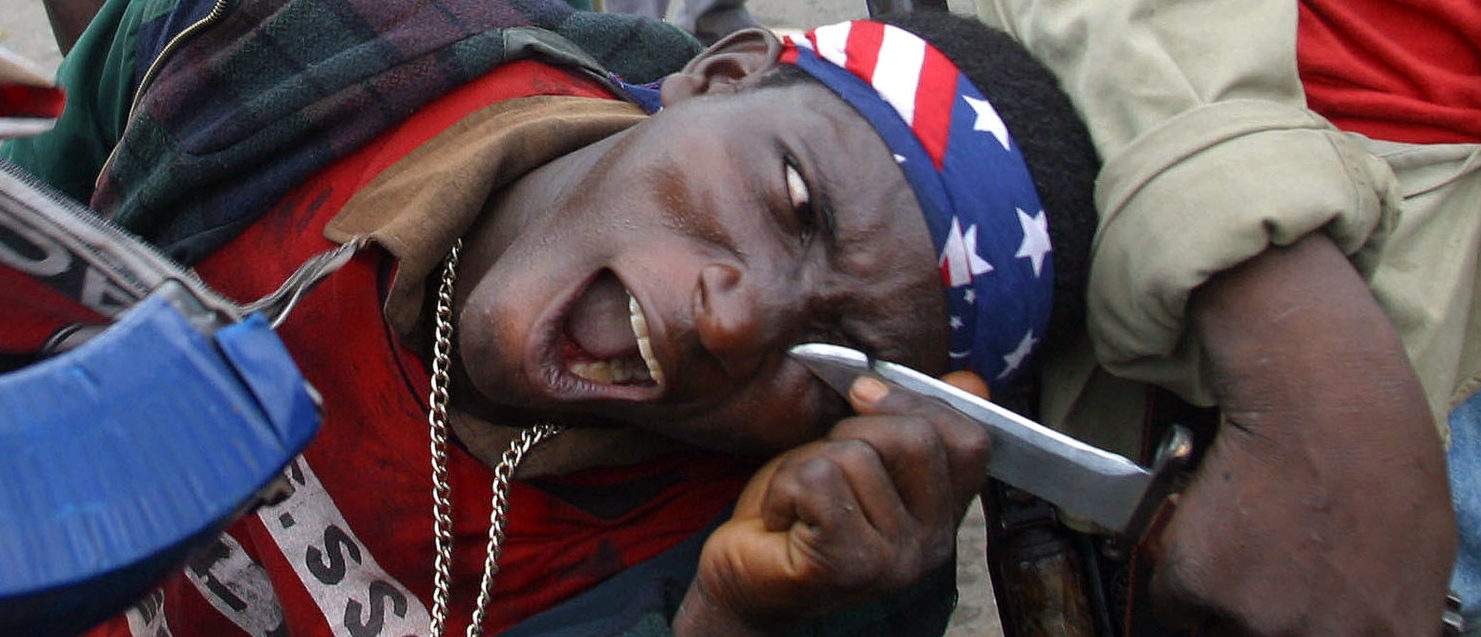 A fighter loyal to Liberia's President Charles Taylor shows his bravado using a comrade's knife as government forces gather on the outskirts of the capital Monrovia to beat off a feared rebel attack, July 18, 2003. REUTERS/Luc Gnago