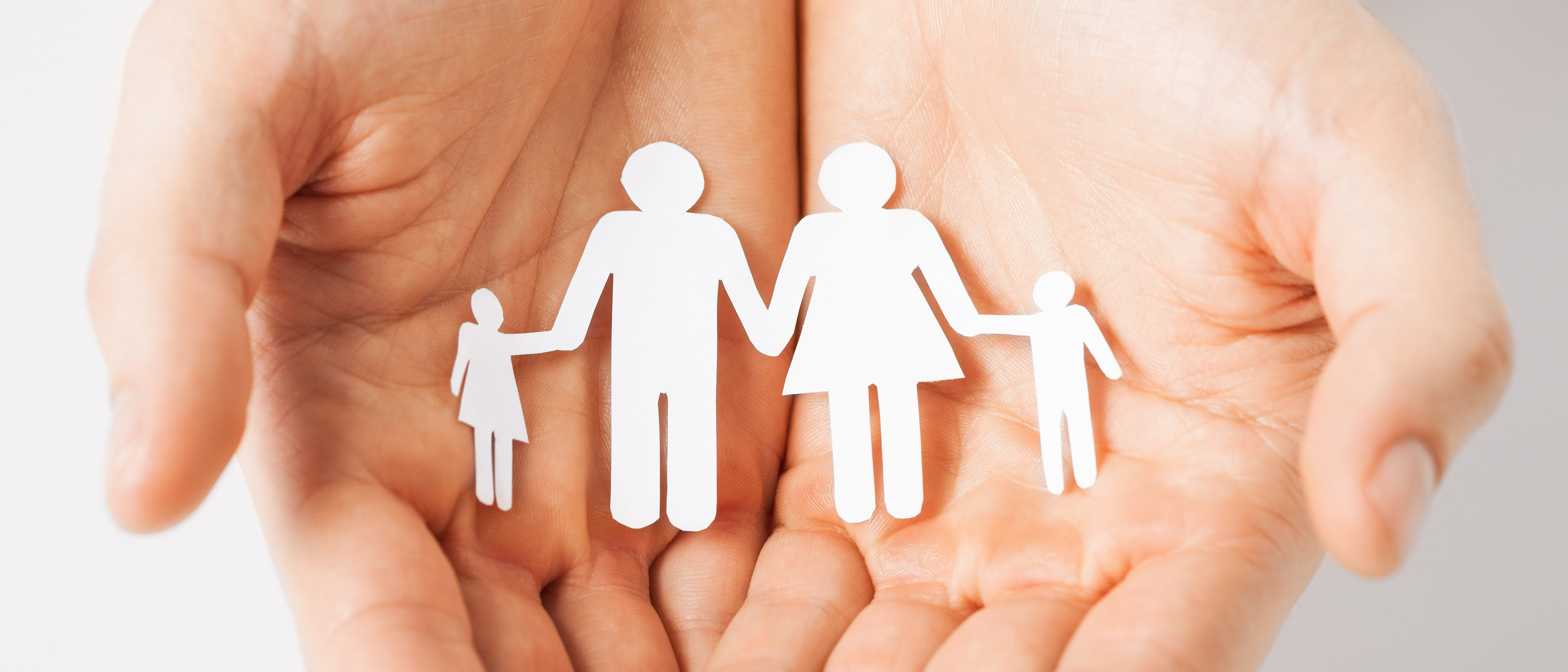 Man hands showing family of paper men. (Shutterstock/Syda Productions)