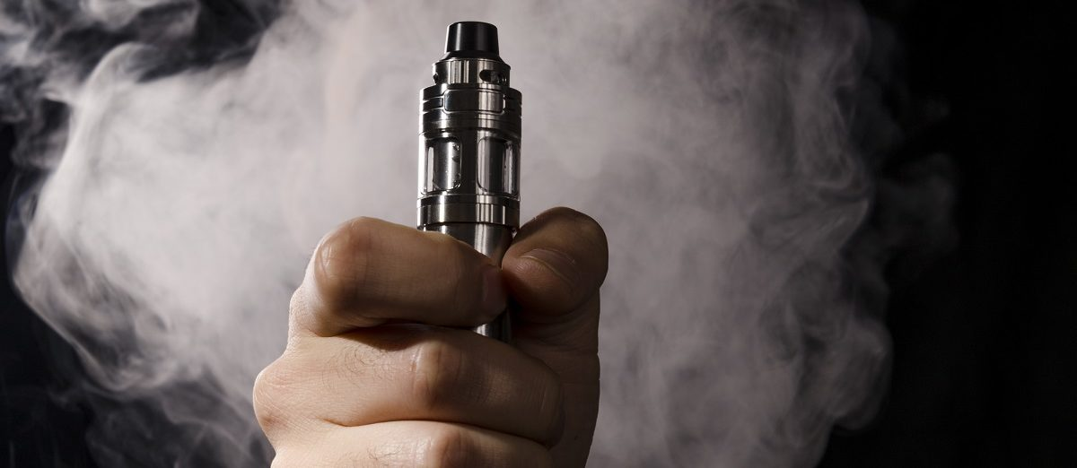 A man is holding an electronic cigarette or vape device with smoke at the background. (Hazem.m.kamal/Shutterstock)