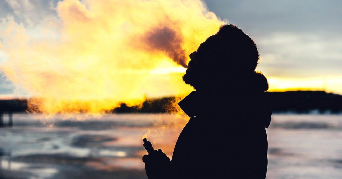 Man with beard smokes electronic cigarette outdoors. (bedya/Shutterstock)