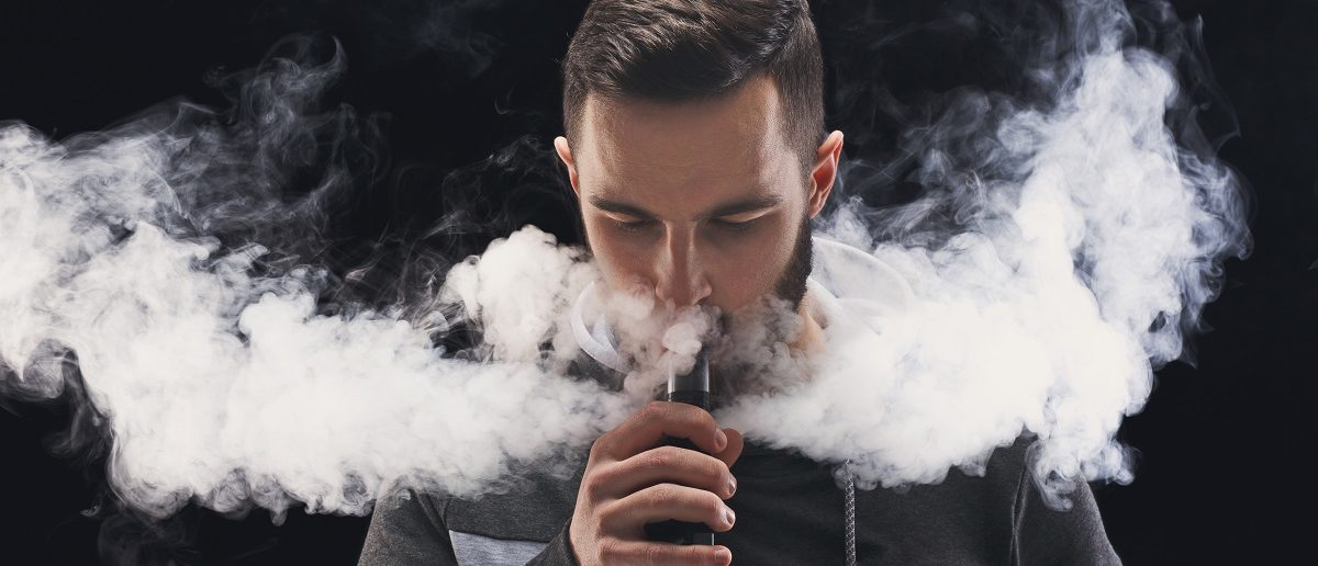Man with vaping mod exhaling steam at black studio background. Bearded guy smoking e-cigarette to quit tobacco. Vapor and alternative nicotine free smoking concept, copy space. (Prostock-studio/Shutterstock)