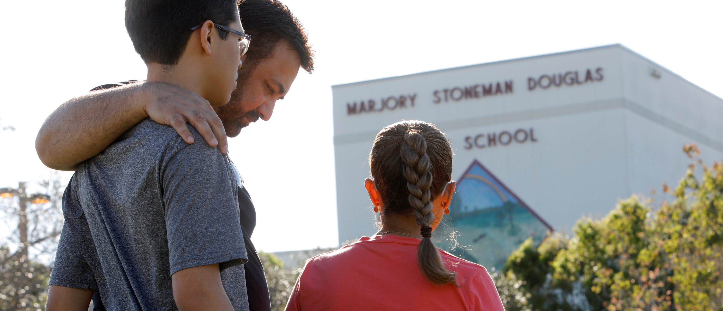 A father and his two children share a moment of reflection at Marjory Stoneman Douglas High School four days after the shooting there, in Parkland, Florida, February 18, 2018. REUTERS/Jonathan Drake