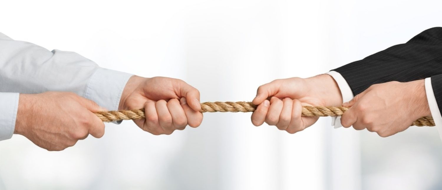 A conflict represented by a tug-of-war struggle. [Shutterstock - Billion Photos]