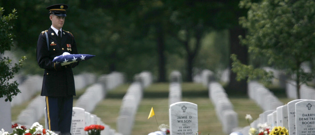 A member of the U.S. Army honor guards stands alongside the plot of Army Sgt 1st Class Greg Sutton during his burial service at Arlington National Cemetery near Washington, June 20, 2007. Sutton, 38, died on June 6 after his vehicle struck an improvised explosive device in Baghdad. REUTERS/Jason Reed