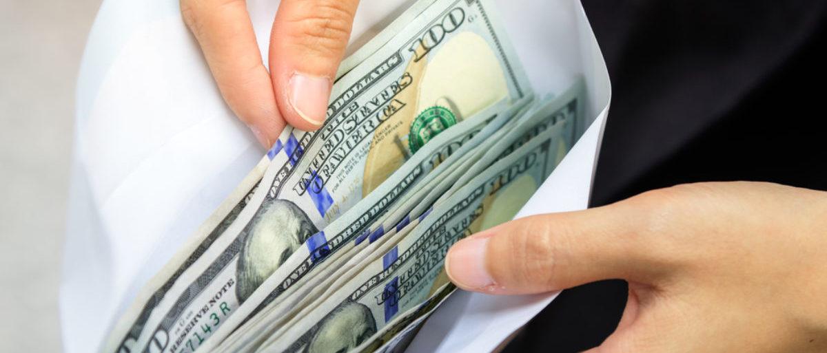 Crisp dollar bills are found in an envelope. (Shutterstock/SOUTHERNTraveler)