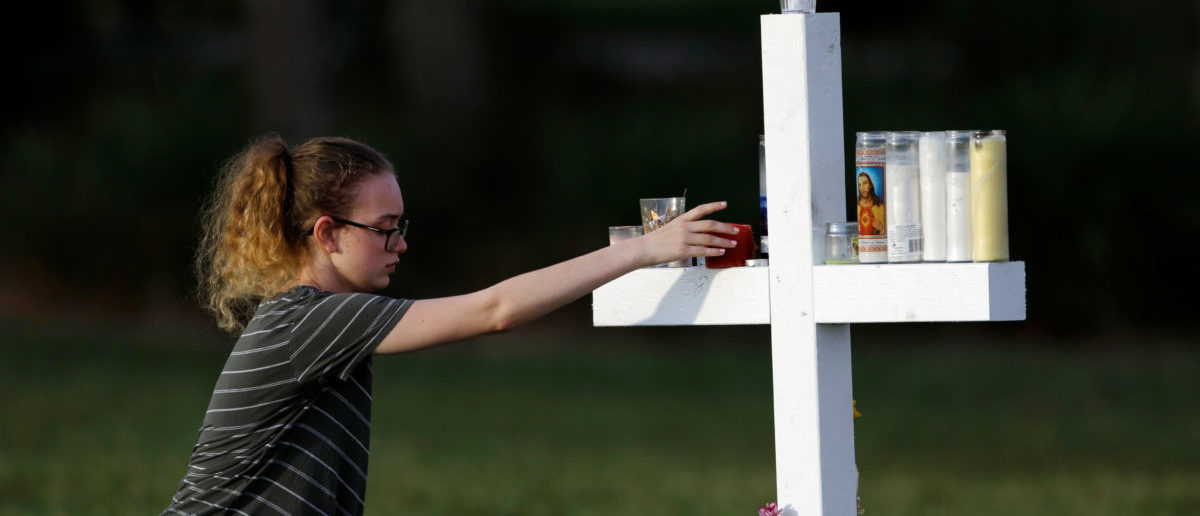 A mourner places a candle on one of 17 crosses at a memorial for the victims of the shooting at Marjory Stoneman Douglas High School in Parkland, Florida, U.S. February 16, 2018.  REUTERS/Jonathan Drake