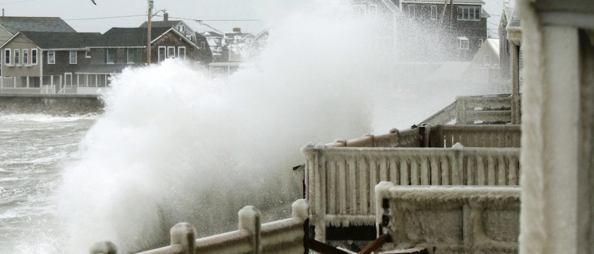 Waves crash into houses on Lighthouse Road during a winter nor'easter snow storm in Scituate, Massachusetts January 3, 2014. A heavy snowstorm and dangerously low temperatures gripped the northeastern United States on Friday, delaying flights, paralyzing road travel, and closing schools and government offices across the region. REUTERS/Dominick Reuter