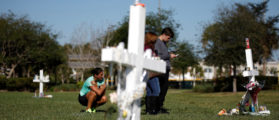 People mourn in front of a cross in a park where crosses were placed to commemorate the victims of the shooting at Marjory Stoneman Douglas High School, in Parkland, Florida, U.S., February 16, 2018. REUTERS/Carlos Garcia Rawlins