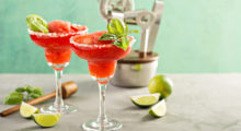 Pink Margarita: 2 parts tequila, 1/2 part campari, 3/4 part lemon juice, 3/4 part honey... Add ice to blender, blend ingredients, strain into cocktail glass, garnish with lime slice and mint leaves.  (Photo credit: Shutterstock)