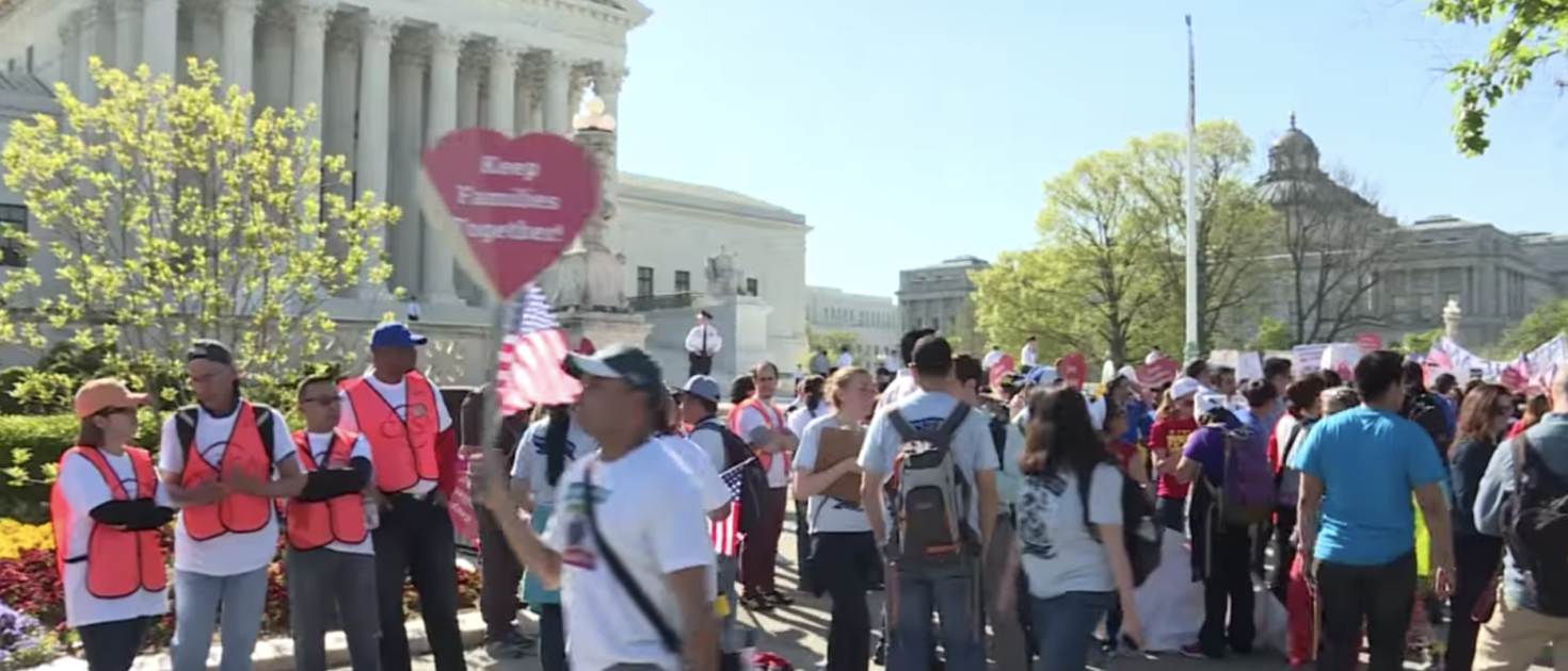 Pro-immigrant groups rally outside the Supreme Court. (YouTube screenshot/AFP news agency)
