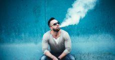 Men with beard vaping outdoor in sunglasses. (bedya/Shutterstock)