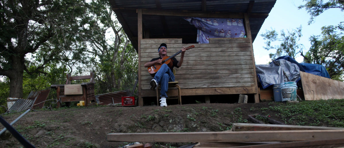 Angel Colon plays the guitar outside a little hut, in which he lives since his house was destroyed, in Comerio