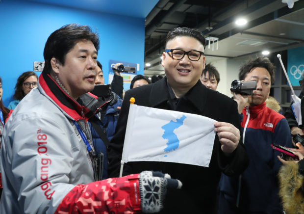 Ice Hockey – Pyeongchang 2018 Winter Olympics – Women Preliminary Round Match - Korea v Japan - Kwandong Hockey Centre, Gangneung, South Korea – February 14, 2018 - Kim Jong-un impersonator holds a Korean unification flag. REUTERS/Lucy Nicholson