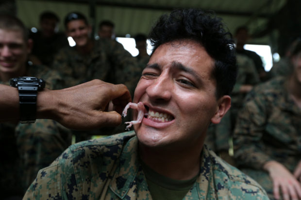 "A U.S. Marine eats a geko during a jungle survival exercise as part of the ""Cobra Gold 2018"" (CG18) joint military exercise, at a military base in Chonburi province, Thailand, February 19, 2018. REUTERS/Athit Perawongmetha"