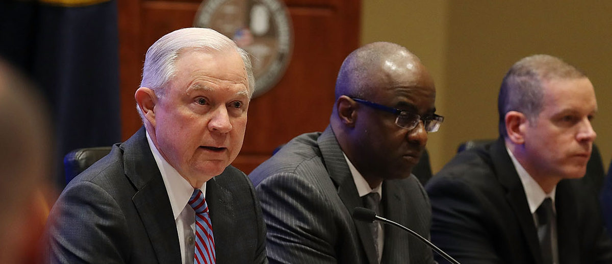 U.S. Attorney General Jeff Sessions (L) joins with Anthony Williams, Drug Enforcement Administration associate administrator, (2nd R) during the opening remarks at the U.S. Southern Command Opioid Summit on February 8, 2018 in Doral, Florida. During the day-long Opioid Summit officials are focusing on the crisis, considering approaches to strengthen the nation's response and define holistic strategies supporting the president's call to action in order to end what he has declared a 'national public health emergency.' (Photo by Joe Raedle/Getty Images)