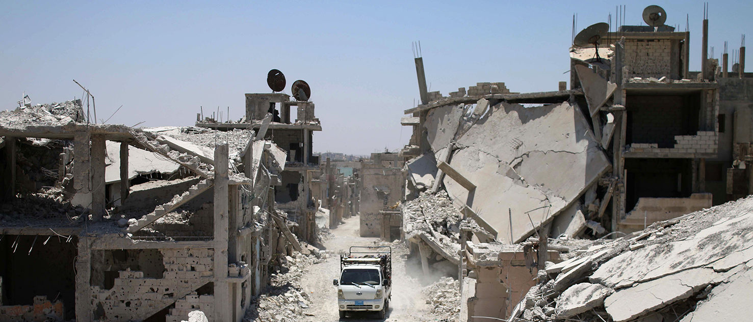 A truck drives down a destroyed street in a rebel-held area in Daraa on July 19, 2017, as civilians started to return to the area following the July 9 agreement ceasefire brokered by the United States, Russia and Jordan creating a de-escalation zone in Syria's southern Daraa, Quneitra and Sweida regions.  MOHAMAD ABAZEED/AFP/Getty Images