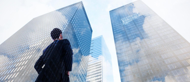 Businessman looking up at large skyscrapers. [Shutterstock - wavebreakmedia]