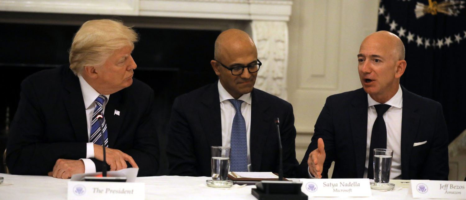 U.S. President Donald Trump and Satya Nadella, CEO of Microsoft Corporation listen as Jeff Bezos, CEO of Amazon speaks during an American Technology Council roundtable at the White House in Washington, U.S., June 19, 2017. REUTERS/Carlos Barria