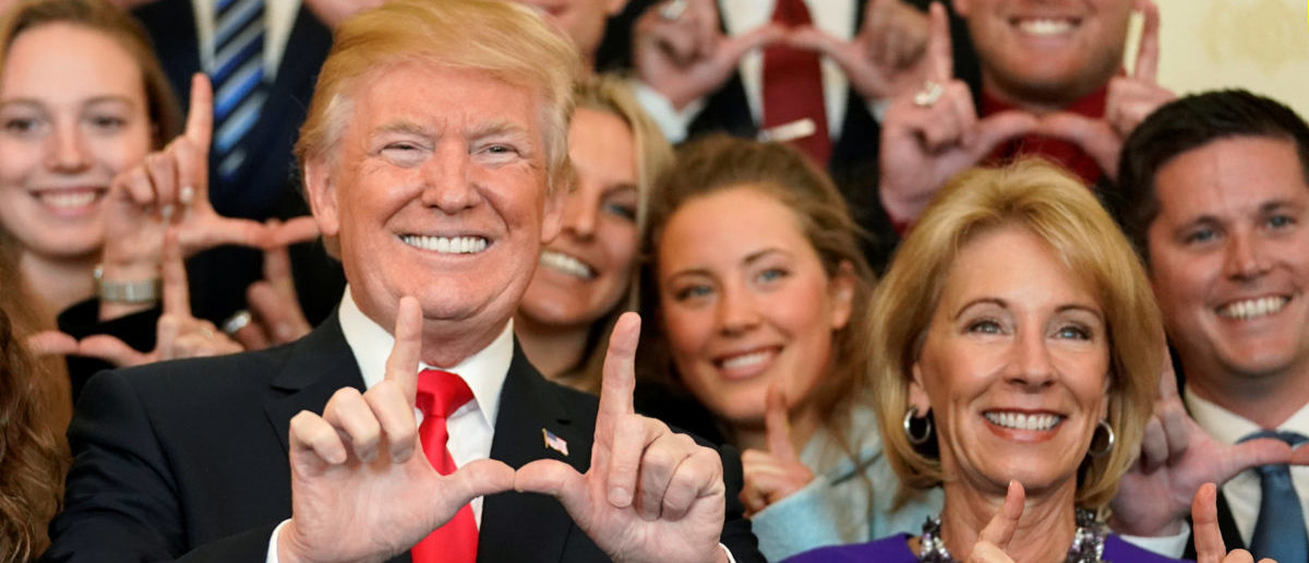"U.S. President Donald Trump and Education Secretary Betsy DeVos make ""U"" symbols with their hands while posing with the Utah Skiing team as they greet members of Championship NCAA teams at the White House in Washington, U.S., November 17, 2017. REUTERS/Joshua Roberts - RC1AE79B5250"