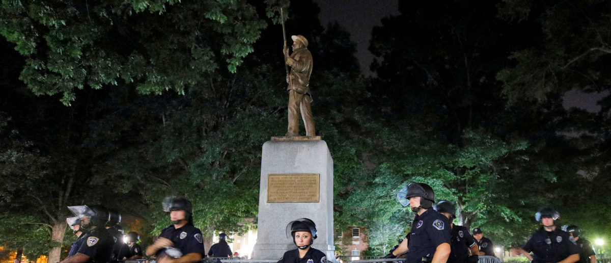 Police wearing riot gear guard a statue of a Confederate soldier nicknamed Silent Sam on the campus of the University of North Carolina during a demonstration for its removal in Chapel Hill, North Carolina, U.S. August 22, 2017. REUTERS/Jonathan Drake