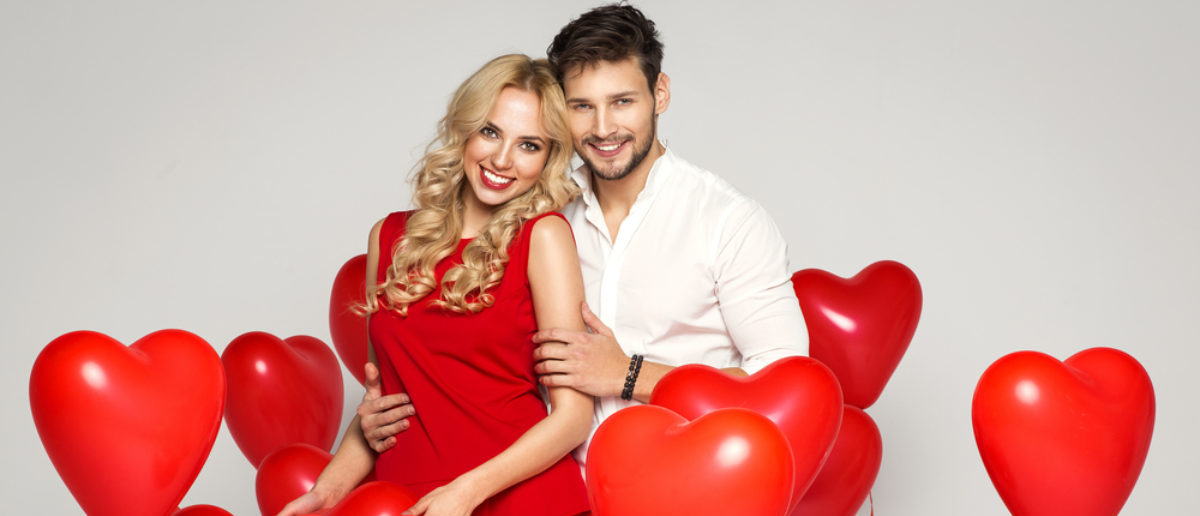 A young, loving couple poses with heart balloons on Valentine's Day. (Shutterstock/kiuikson)