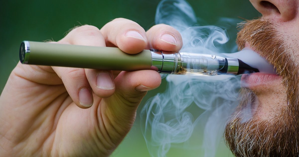 Close-up of a man vaping an electronic cigarette. Bruxelle/Shutterstock