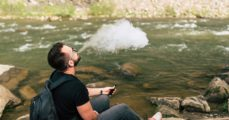 Traveler smoke electronic cigarette near mountain river. (bedya/Shutterstock)