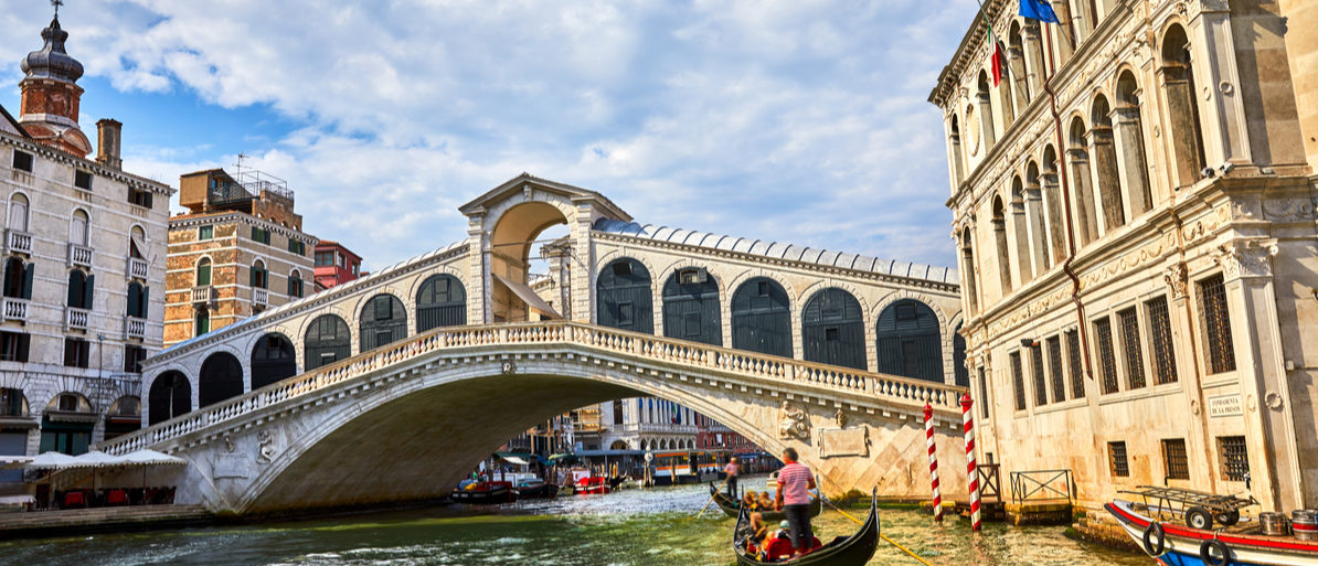 Bridge Rialto on Grand canal famous landmark panoramic view Venice Italy with blue sky white cloud and gondola boat water Shutterstock/ Yasonya