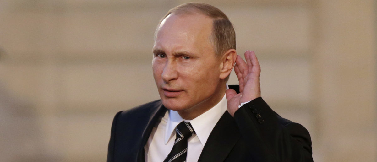 Russian President Vladimir Putin cups his ear to listen to a question as he departs after a summit on the Ukraine crisis at the Elysee Palace in Paris, France, October 2, 2015. France hosted a meeting with leaders of Russia, Germany and Ukraine in Paris for talks about Ukraine which were likely to be overshadowed by the conflict in Syria. REUTERS/Philippe Wojazer