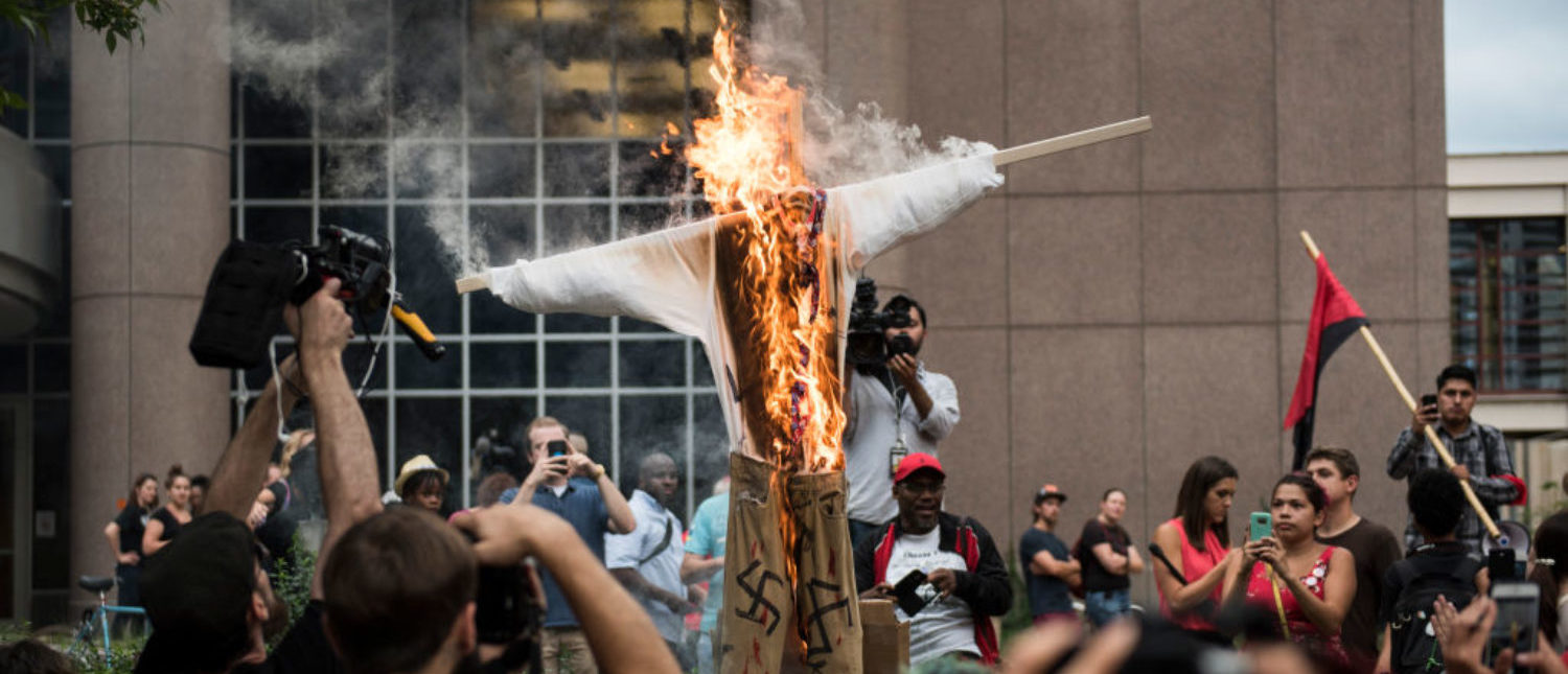 MINNEAPOLIS, MN - AUGUST 14: An effigy of U.S. President Donald Trump, dressed in khakis and a white shirt covered in swastikas, is set ablaze during a protest against racism and the violence over the weekend in Charlottesville, Virginia on August 14, 2017 in Minneapolis, Minnesota. Protesters estimated at more than 1,000 blocked streets and light rail during the action. (Photo by Stephen Maturen/Getty Images)