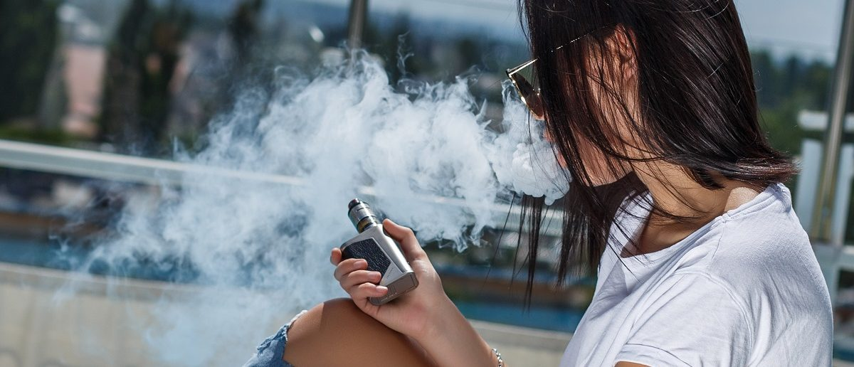 Young sexy woman is sitting near the swimming pool relax and vape. Lady in sunglasses. Summer. (Ostancov Vladislav/Shutterstock)