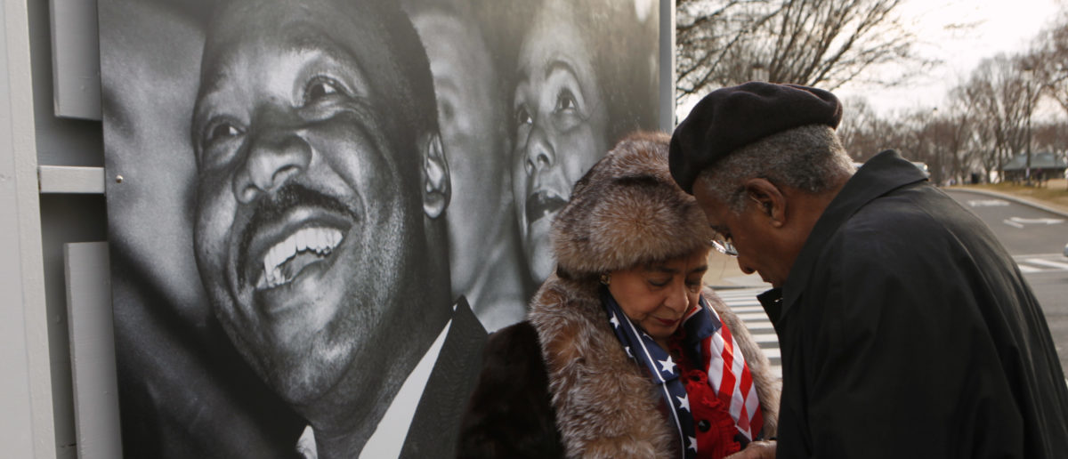 In front of a photo of Dr. Martin Luther King Jr. and Coretta Scott King, James and Jewelle Gibbs of Oakland, CA, find their IDs for entry to the ground breaking ceremony for the Smithsonian National Museum of African American History and Culture on the National Mall in Washington February 22, 2012. REUTERS/Kevin Lamarque