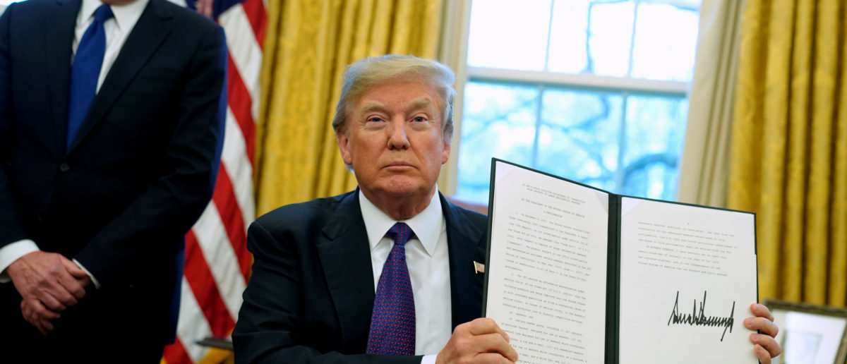 FILE PHOTO: U.S. President Donald Trump, flanked by U.S. Trade Representative Robert Lighthizer, holds up a directive to impose tariffs on imported washing machines after signing it in the Oval Office at the White House in Washington, U.S. January 23, 2018. REUTERS/Jonathan Ernst/File Photo