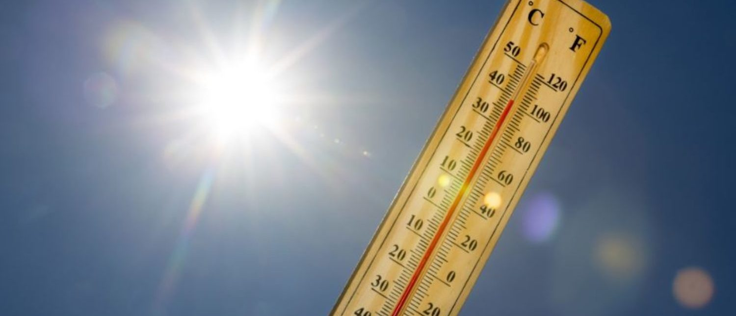 Mercury thermometer marking 39 degrees Celsius 100 Fahrenheit in a sunny day. Summer heat shown on mercury thermometer against the blue sky. Sunlight with sun flares. (shutterstock/Belish)