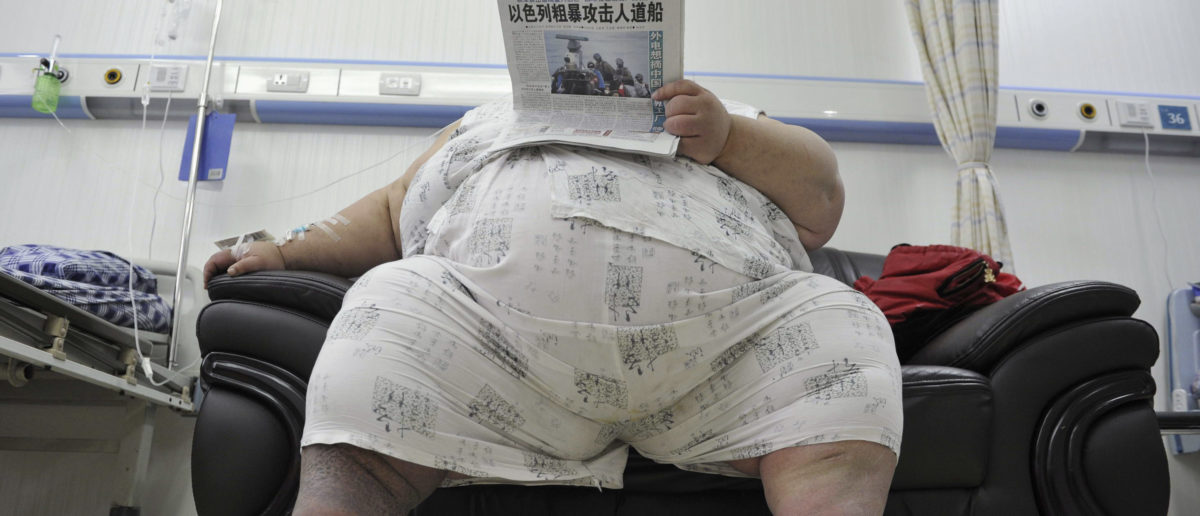Liang Yong, 30, who weighs about 230 kg (507 lbs) and is 1.58 m (5.18 ft) tall, reads newspaper in a ward at a hospital in Chongqing municipality June 1, 2010. Liang, who has suffered from obesity since 1998 and has unsuccessfully tried different methods of losing weight, is in a critical health condition due to his weight, and has been warded in the intensive care unit since last week, local media reported. REUTERS/Stringer