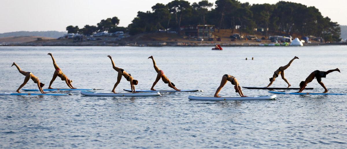 People practise Metta Float Yoga at the adriatic cost in Medulin, Croatia August 6, 2015. REUTERS/Pawel Kopczynski