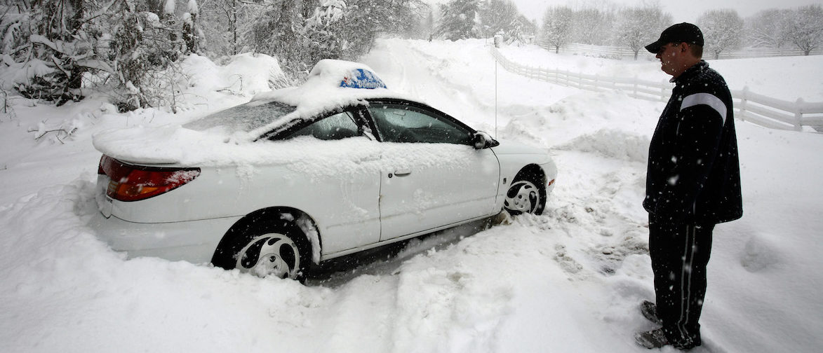 A Domino's Pizza delivery man ponders his next move after his vehicle got stucked on a snow-covered road in Great Falls, Virginia, February 6, 2010. A blizzard producing heavy snow and powerful winds pummeled the U.S. mid-Atlantic on Saturday, causing at least two fatalities and paralyzing travel in the region. Snowfall totals of 20 to 30 inches (51 to 76 cm) are forecast from Virginia to southern New Jersey by Saturday evening when the storm is expected to move out to sea. REUTERS/Hyungwon Kang    (UNITED STATES - Tags: ENVIRONMENT TRANSPORT) - GM1E62705BI01
