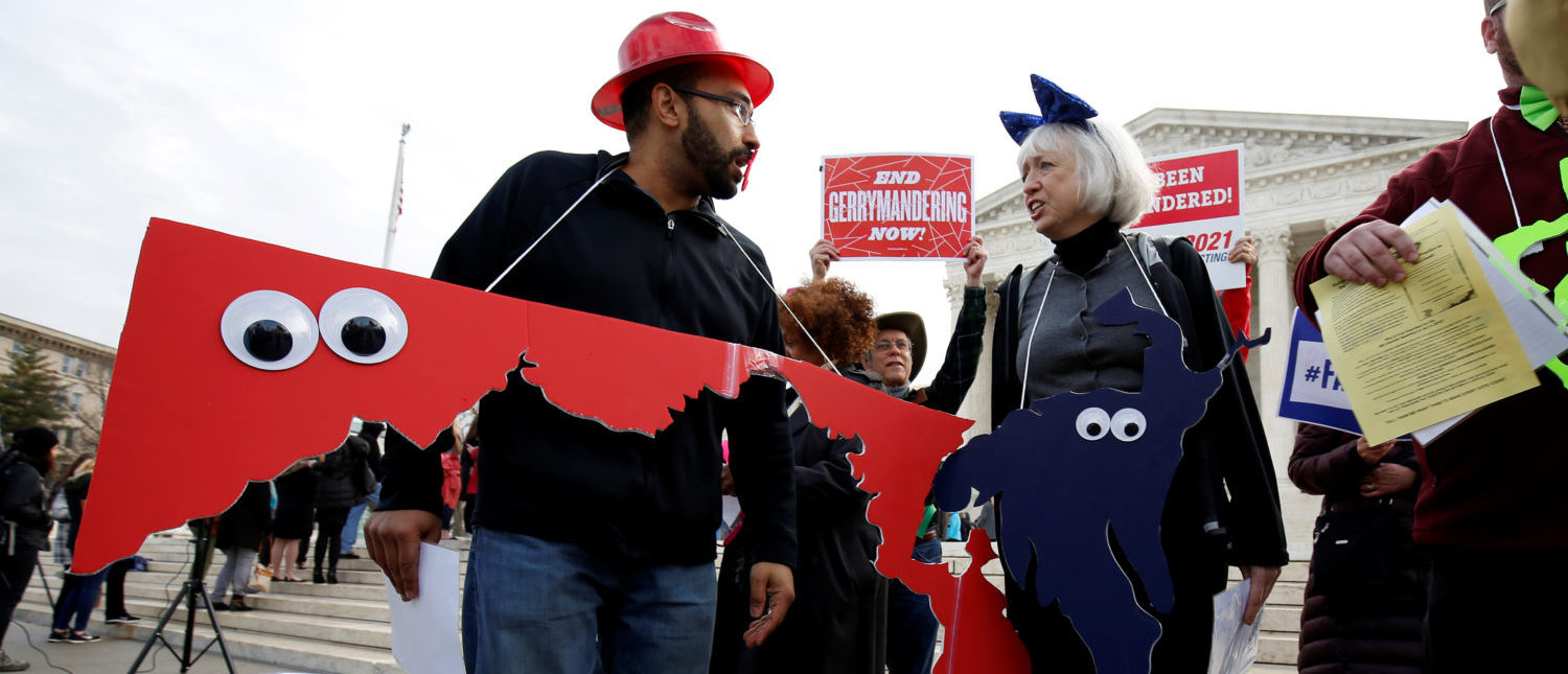Demonstrators rally with cut-outs of congressional districts in front of the Supreme court before oral arguments on Benisek v. Lamone, a redistricting case on whether Democratic lawmakers in Maryland unlawfully drew a congressional district in a way that would prevent a Republican candidate from winning, in Washington, U.S., March 28, 2018. REUTERS/Joshua Roberts | SCOTUS No Closer On Partisan Gerrymanders
